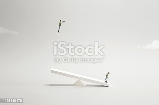 istock two men playing with catapult to get higher point of view to see the future with telescope 1158149479