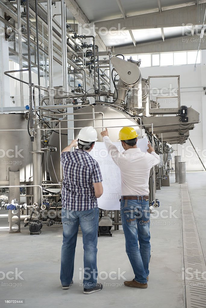 Two men pointing at machinery stock photo