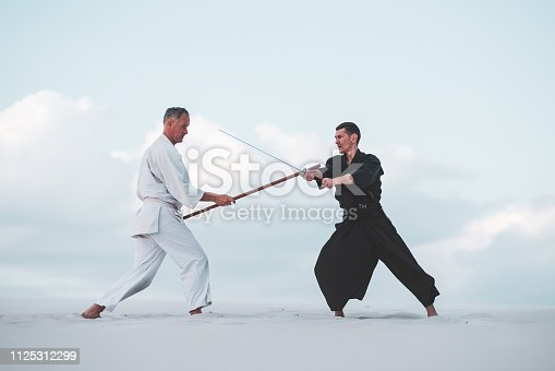 Two men, in Japanese clothes, are practicing martial arts with a traditional Japanese weapon - a katana and jo,  in the desert at sunset.