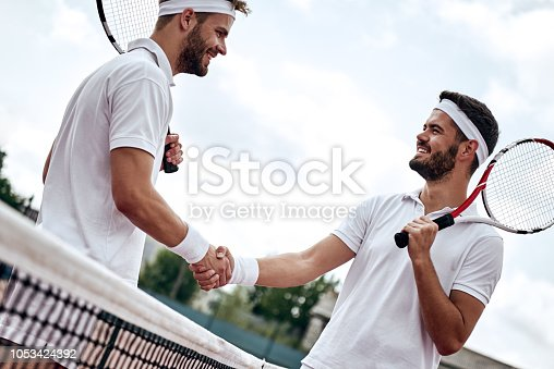 istock Two men, professional tennis players shake hands before and after the tennis match. One of they has the face of anger. He is trying to intimidate his opponent. 1053424392