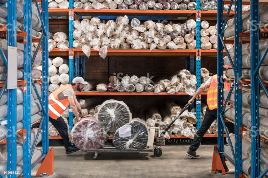 Two men pulling trolley with carpets in warehouse stock photo