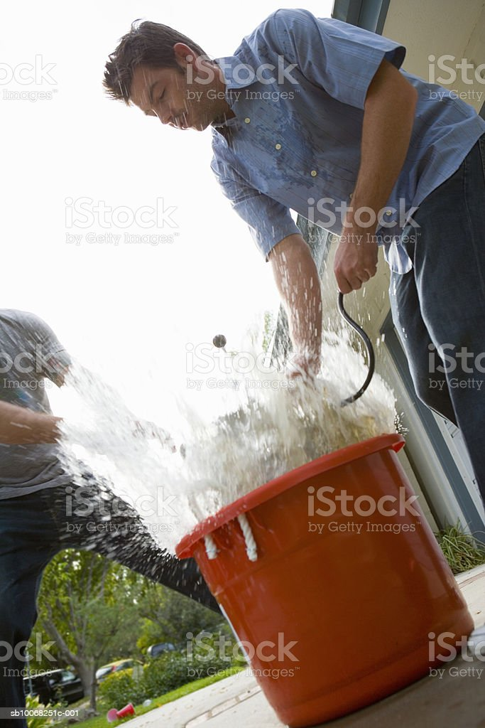 Two men putting beer keg into bucket royalty-free stock photo