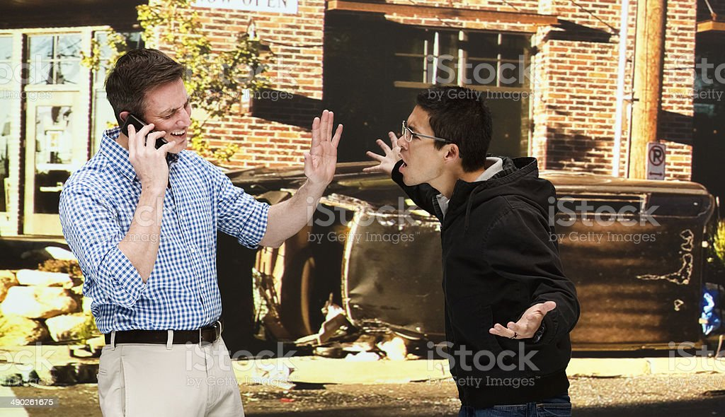 Two men quarreling at car crash site stock photo