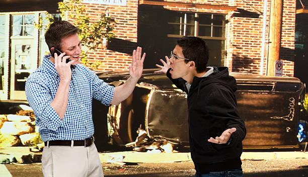 Two men quarreling at car crash site stock photo