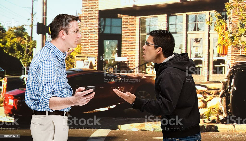 Two men quarreling in front of car accident stock photo