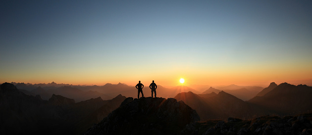 Happy winning success men at sunset or sunrise standing relaxed and are happy for having reached mountain top summit goal during hiking travel trek. Tirol, Austria. Allgau, Bavaria.