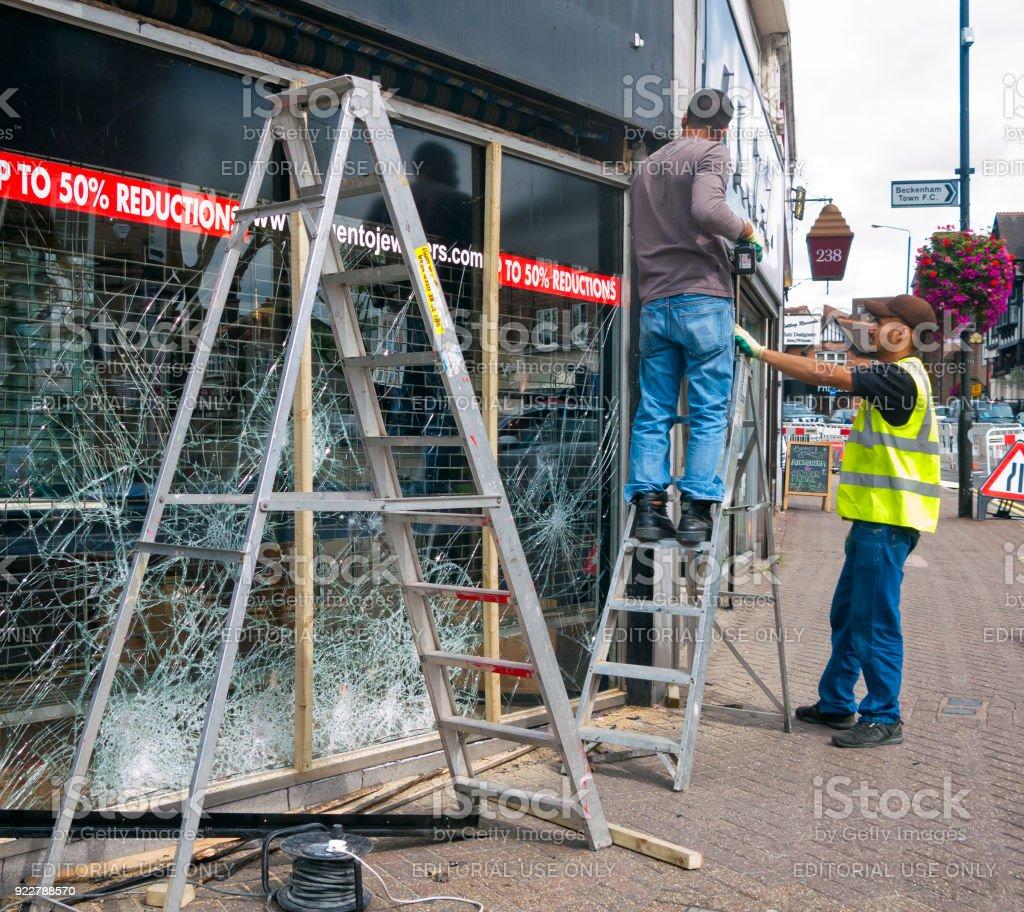 Two men repairing a vandalised window stock photo
