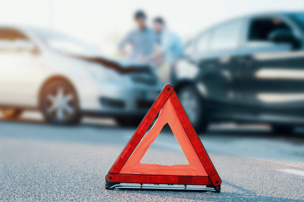 Two men reporting a car crash for insurance claim Two men reporting a car crash for the insurance claim,main focus on red triangle misfortune stock pictures, royalty-free photos & images