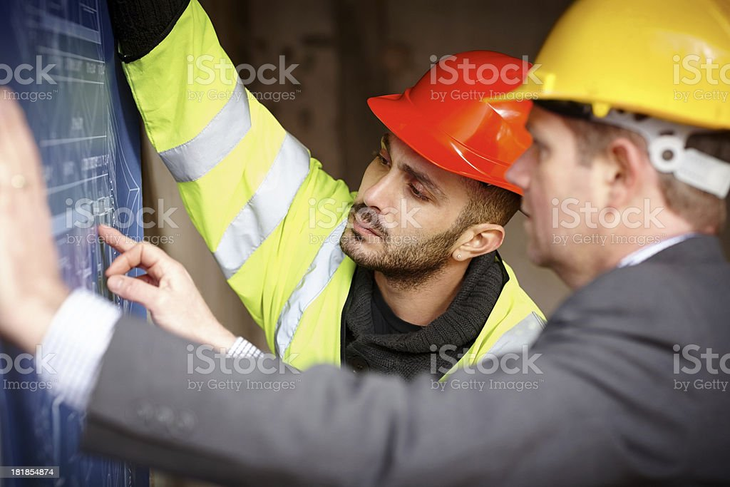 Two men reviewing blueprints on construction site royalty-free stock photo