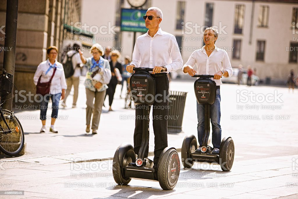 Two men riding Segway through Piazza del Duomo, Milan, Italy royalty-free stock photo
