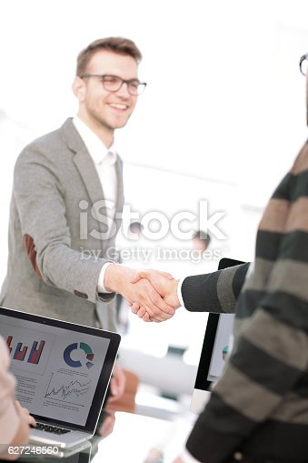 istock Two men shaking hands and looking at each other with 627246560