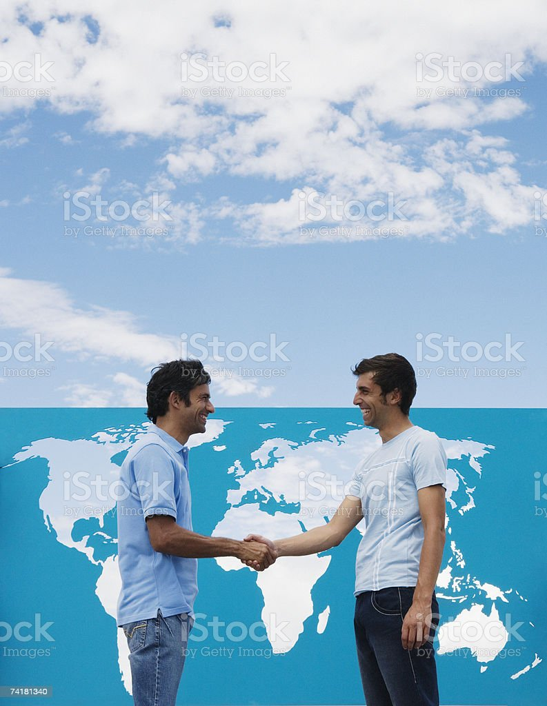 Two men shaking hands in front of world map outdoors royalty-free stock photo