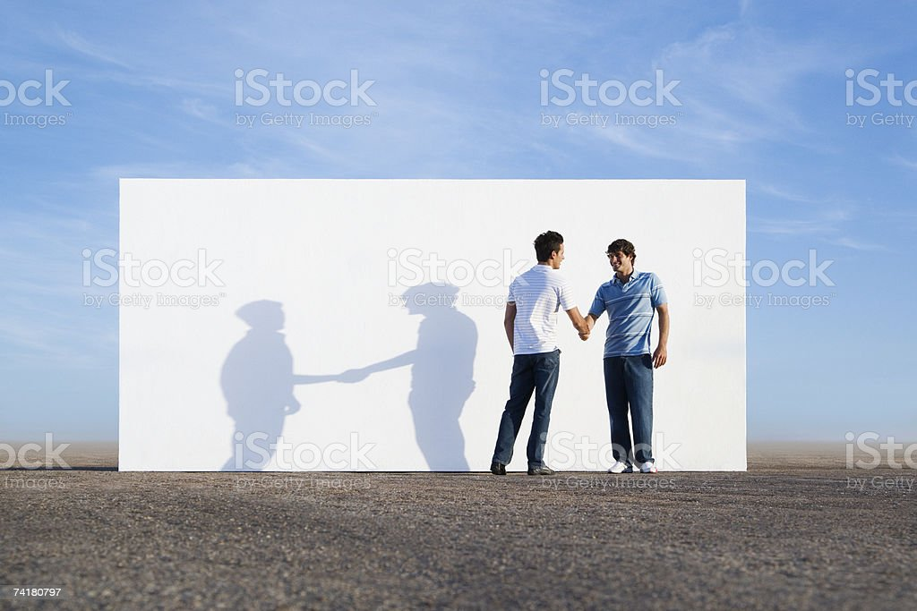 Two men shaking hands outdoors with wall royalty-free stock photo