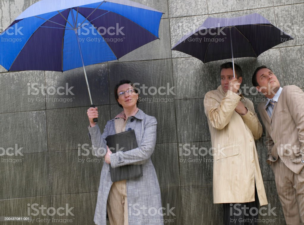 Two men sharing umbrella in rain next to woman under large umbrella royalty-free stock photo
