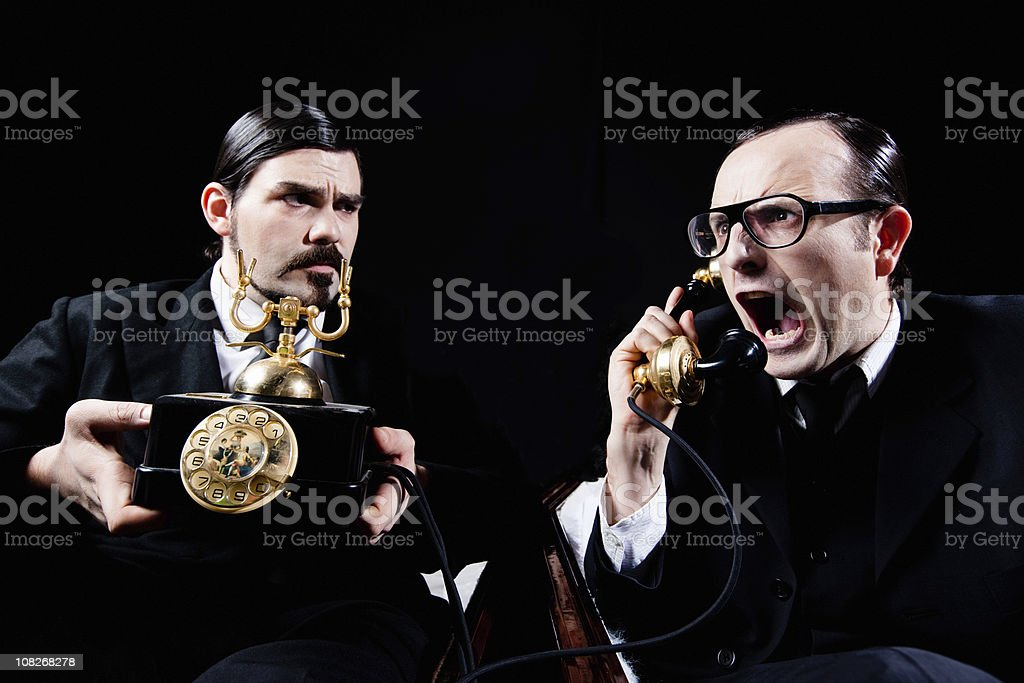 Two Men Shouting into Telephone royalty-free stock photo