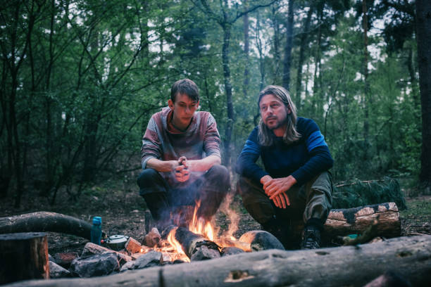 Two men sitting around campfire in spring forest. stock photo