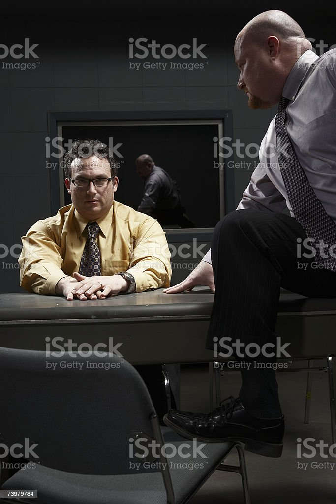 Two men sitting at desk in interrogation room stock photo