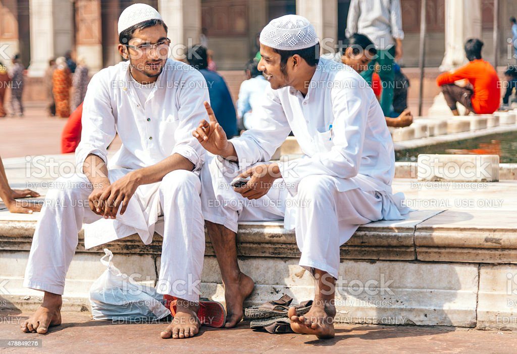 two men sitting at the Jama Masjid Mosque, India stock photo