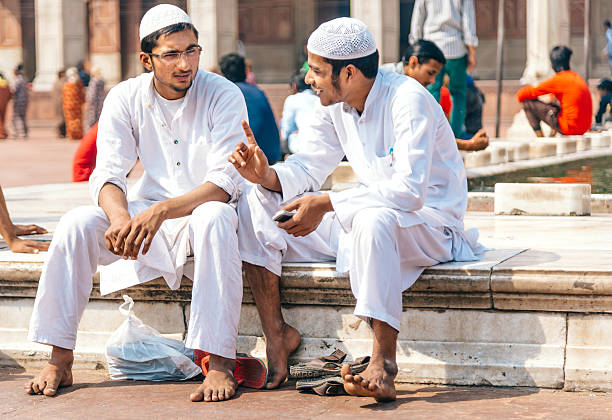 two men sitting at the Jama Masjid Mosque, India New Dehli, India - March 9, 2014: Two muslim men are sitting and talking in the premises of the jama masjid mosque. Jama Masjid is the largest mosque in India with millions of visitors each year.  agra jama masjid mosque stock pictures, royalty-free photos & images
