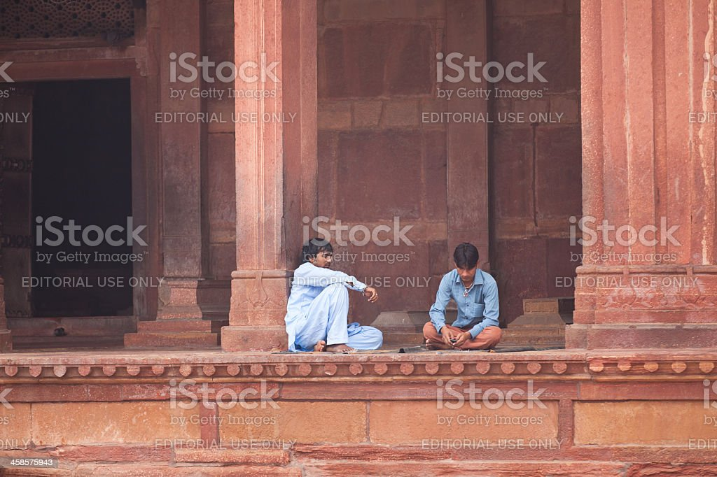 two men sitting at the jama masjid mosque stock photo