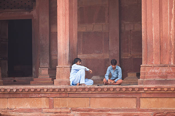 two men sitting at the jama masjid mosque Fatehpur Sikri, Agra district, India - November 17, 2010: Two men are sitting and talking in the premises of the jama masjid mosque in fatehpur sikri, agra, india. agra jama masjid mosque stock pictures, royalty-free photos & images