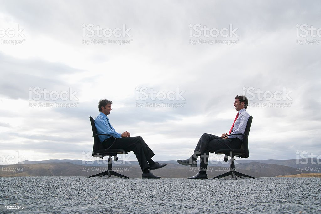 Two men sitting in office chairs outdoors  stock photo
