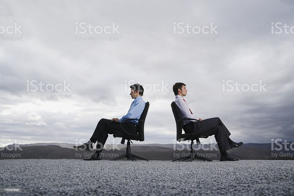 Two men sitting in office chairs outdoors with their backs against one another stock photo