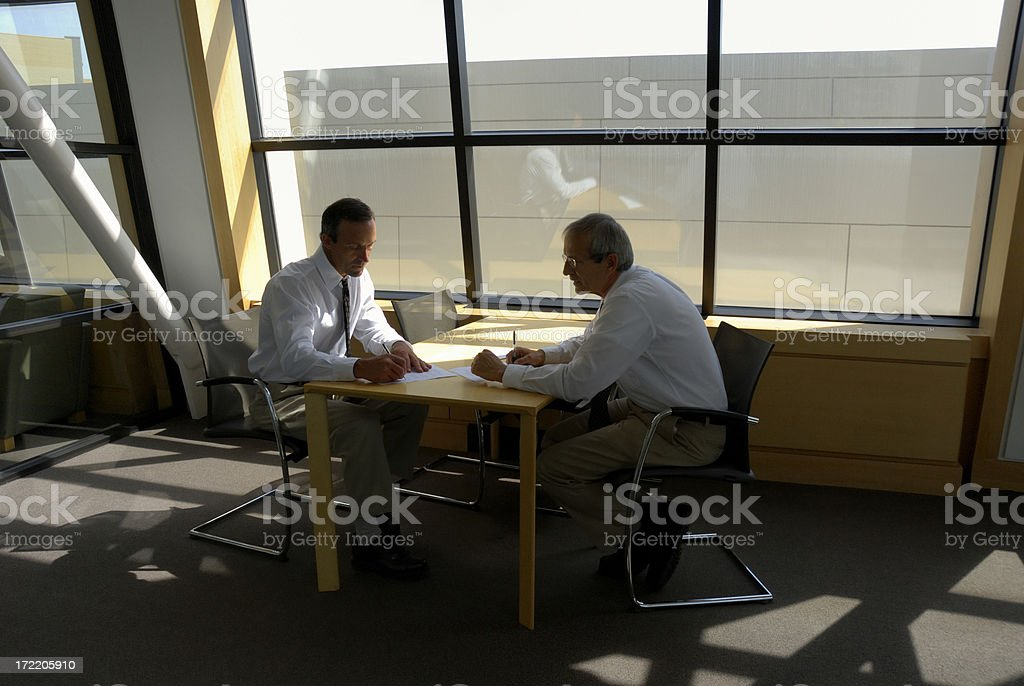 Two men sitting on a desk by the window signing contract royalty-free stock photo