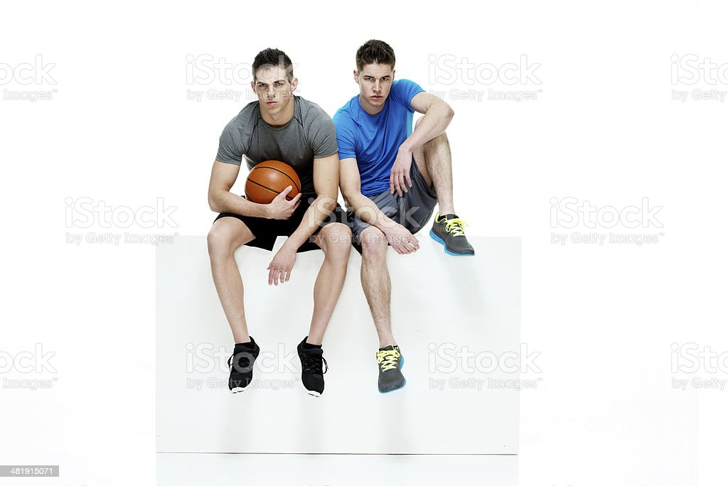 Two men sitting on box and holding basketball royalty-free stock photo