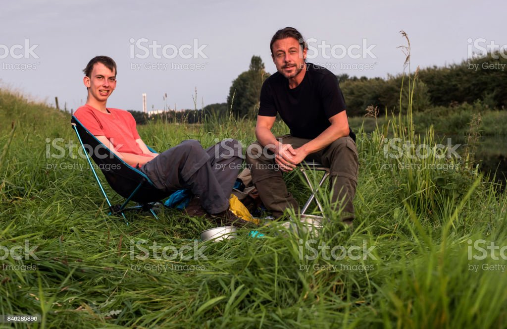 Two Men Sitting On Chair In Tall Grass Enjoying Nature Stock