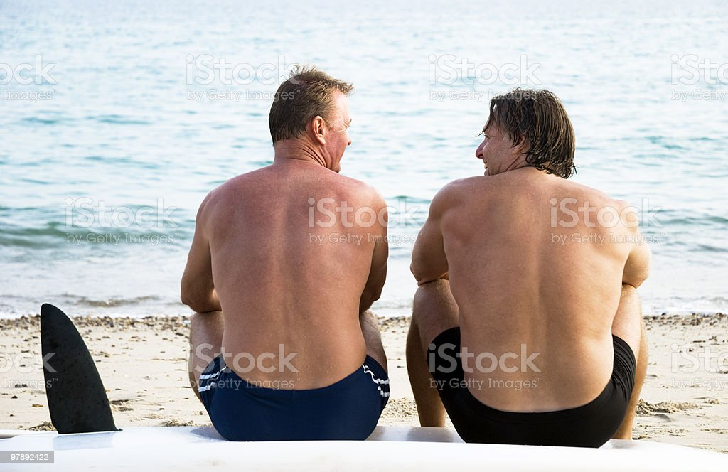 Two men sitting together on beach. stock photo
