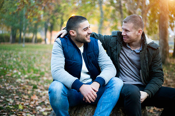 Two men smaling in park about something - Photo