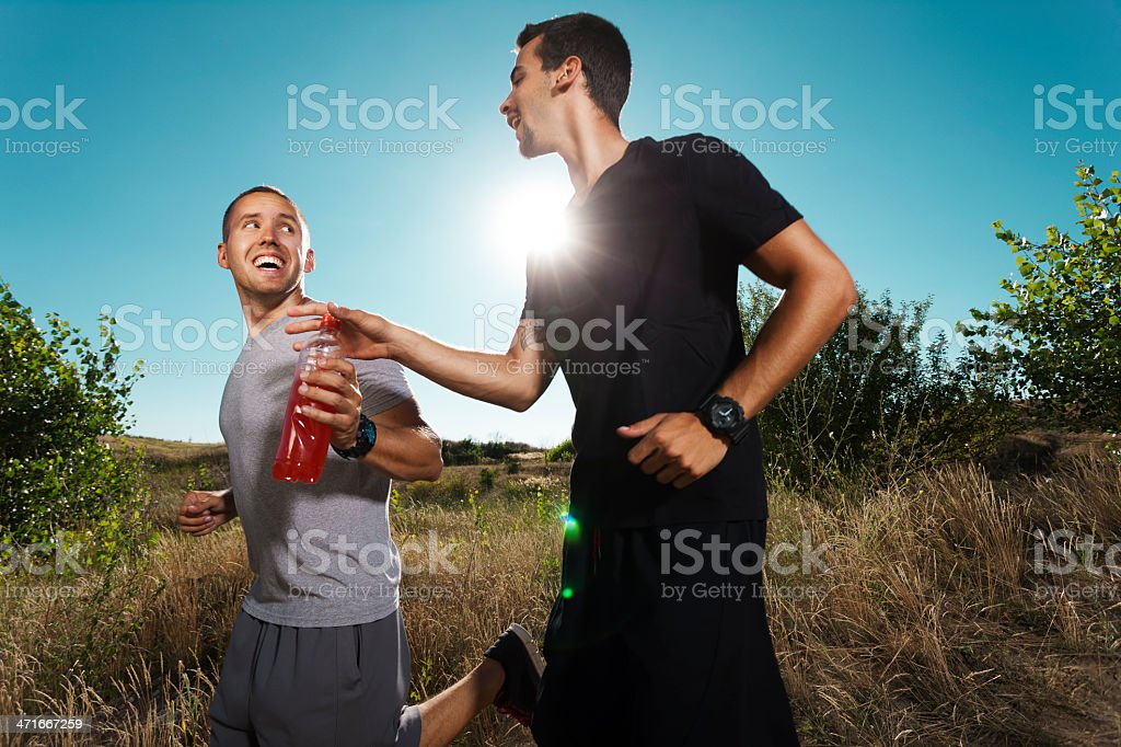 Two men smiling while they are jogging in an open field royalty-free stock photo
