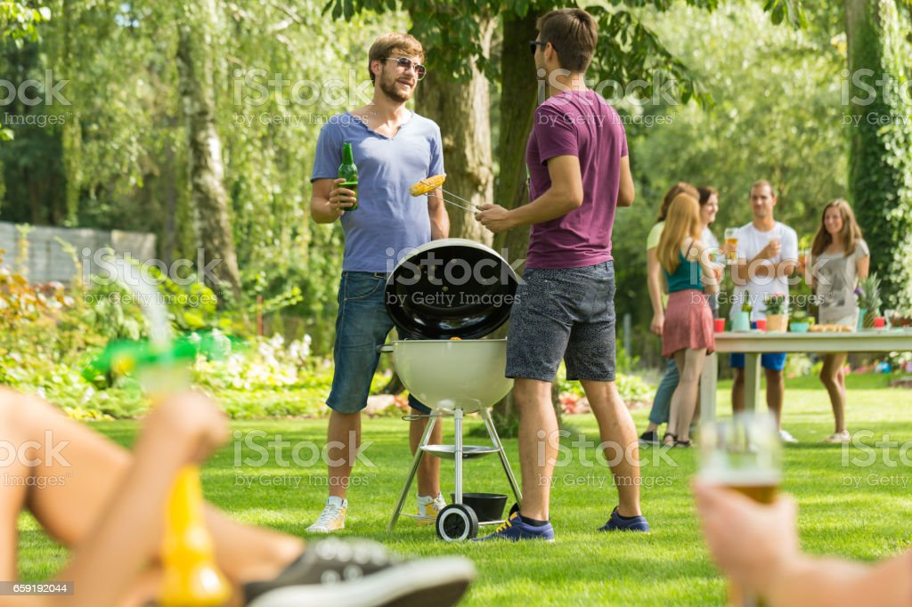 Two men standing beside grill stock photo