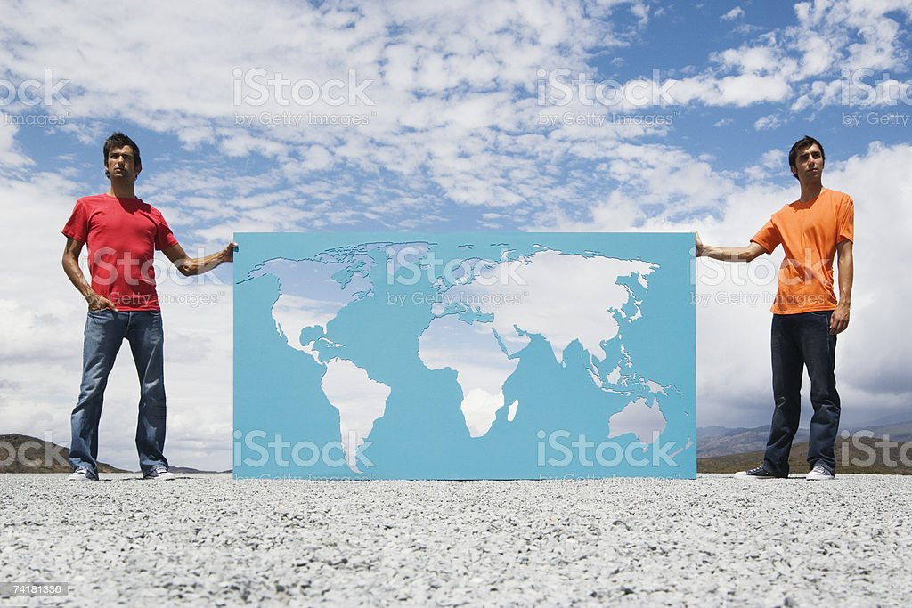 Two men standing beside world map outdoors royalty-free stock photo