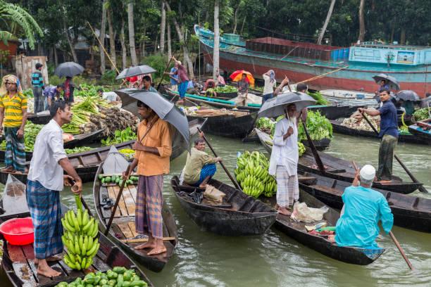 Barisal, Bangladesch - 12. Juli 2016: Zwei Männer stehen in Booten, Verhandlungen über den Verkauf von Bananen am schwimmenden Gemüsemarkt – Foto