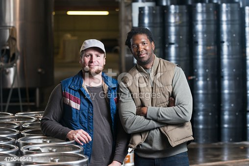 Two multi-ethnic men standing together in the storage warehouse of a manufacturing plant in front of steel drums and storage tanks.  This is a microbrewery where craft beer is produced.