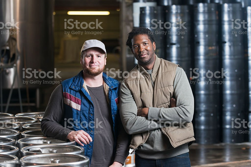 Two men standing in storage warehouse with steel drums stock photo