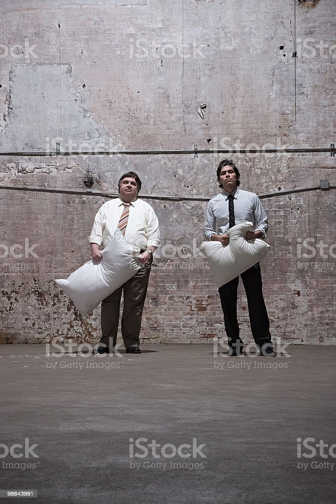 Two men standing in warehouse with pillows 免版稅 stock photo