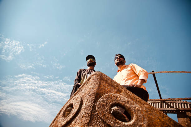 Two men standing on an old metallic boat stock photo