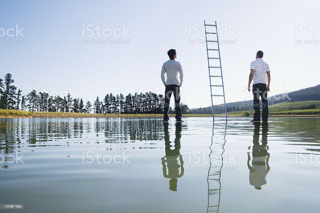 Dois homens de pé na água com escadas foto de stock royalty-free