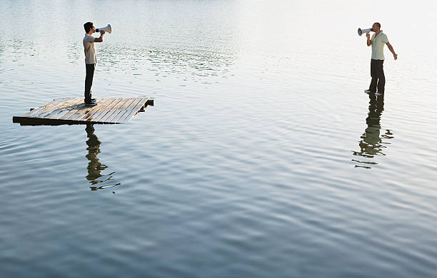 Two men standing on water with megaphones stock photo