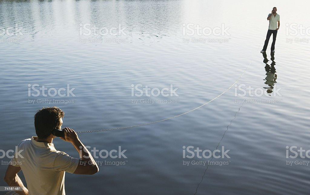 Dois homens de pé na água com receptores e telefone foto de stock royalty-free