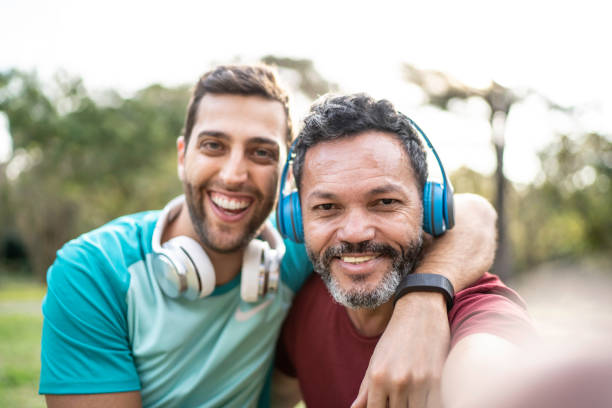 Two men taking a selfie in park Two men taking a selfie in park age contrast stock pictures, royalty-free photos & images