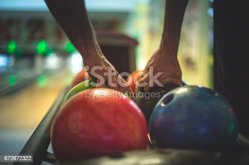 Colorful image of a few bowling balls in a row and two men are taking their balls to throw