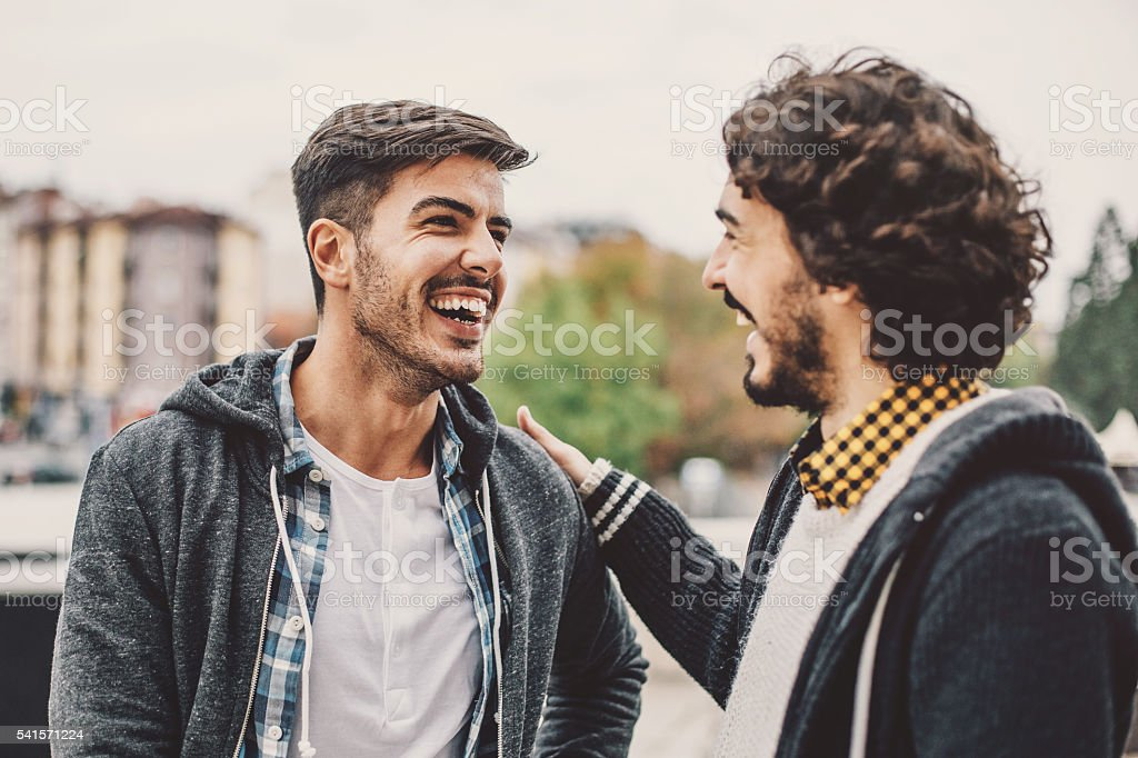 Two men talking and smiling on the street stock photo