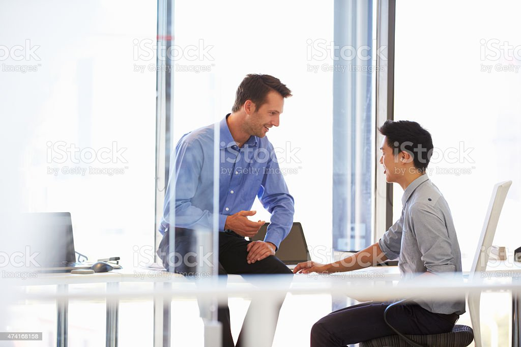 Two men talking in a modern office stock photo