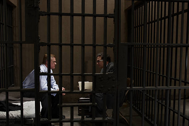 Two men talking in prison cell, side view stock photo