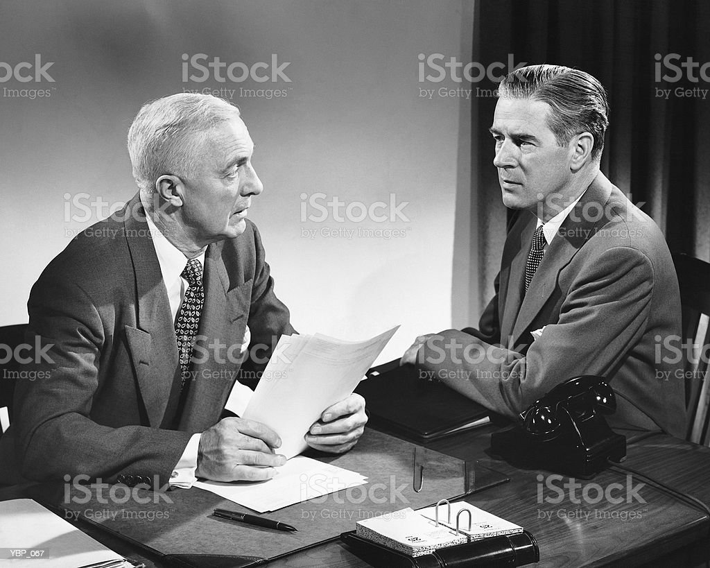 Two men talking, one holding paper royalty free stockfoto