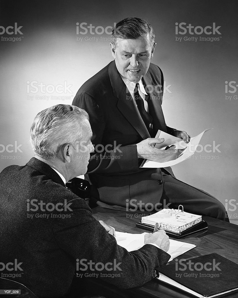 Two men talking, one sitting on desk royalty-free stock photo